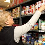 Volunteer Rita Starziski selects cans of soup from the pantry.