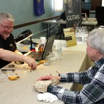 David Whisman, field buyer with the Ohio Valley Rifinery, shifts through some coins and jewlery brought in by Goshen resident Martha Tillmann Jan. 27 at the American Legion Post 17.