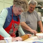 Pie-baking veteran Nancy Maximenko, left, shows newcomer Bob Schlump how to roll the crust Nov. 11 at St. Michael's Church.   PHOTOS BY LARAINE WESCHLER