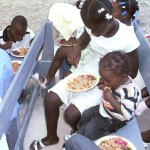 A girl feeds her little brother through a food program in Haiti. The program feeds about 200 children in a weekend.