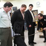 Naugatuck police officer Kevin Zainc, right, leads police K-9 Pete to find drugs planted in the pocket of Dean of Students John Dellacamera, center, flanked by Board of Education member James Scully, left, and Mayor Robert Mezzo during a demonstration at the Board of Education meeting Dec. 12.