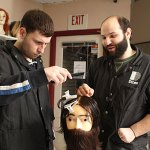 Daniel DiLeo, right, teaches Mike Santos a lesson on hair styling Tuesday afternoon at DiLeo's School of Hair Design in Naugatuck. DiLeo and his family own and operate the barber shop and school. - LARAINE WESCHLER