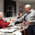 Robert Hiscox gives an American flag to Town Council Chair Tom Galvin during the March 6 council meeting. Hiscox sought and received approval to establish a flag fund through Town Hall to raise money to buy flags for downtown. -LARAINE WESCHLER