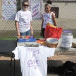 Naugatuck High School senior Lizzie Glick, left, and freshman Abby Karbowicz sell T-shirts, cards and raffle tickets for the softball team's Crush for a Cure program on Monday afternoon at the school. According to the high school's website, the softball program teamed up with Coaches vs. Cancer and the American Cancer Society to host Cancer Awareness events throughout this week. Both varsity and junior varsity teams wore pink socks for breast cancer awareness and lavender Crush for the Cure shirts during games for universal cancer awareness. – Photo by Luke Marshall