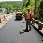 Deziel Paving and Construction employee Thomas Lane checks the asphalt on the streetscape in Beacon Falls last Friday after his co-worker Rob Savoy used a steam roller to flatten it. –LUKE MARSHALL