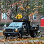 Naugatuck public works employee Don Shae rides in the back of a truck Monday morning on the Naugatuck Town Green. Shae along with Public Works Superintendent Robert Roland (driving the truck) drove along the Green removing American flags from lamp posts in anticipation of heavy winds from Hurricane Sandy. –LUKE MARSHALL