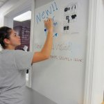 Steph Lima, 18, a senior at Naugatuck High School, writes on 'whiteboard paint' on a wall outside the school store. The school is testing the paint for possible use when the school is renovated and receives new wirelessly networked high-definition projectors. –RA ARCHIVE