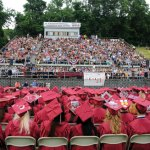 The Naugatuck High School Class of 2012 sits on the football field at the school during graduation last June. This year's graduation ceremony for the Class of 2013 has been moved to the Palace Theater in Waterbury due to ongoing construction at the school. –FILE PHOTO