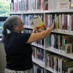 Beacon Falls Library Director Marsha Durley stocks shelves at the library in July. Durley has retired after more than 14 years at the library. –FILE PHOTO