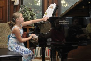 Emily Lungarini plays piano to a roomful of people in 2013 at the Howard Whittemore Memorial Library in Naugatuck. The annual recital is a tribute to Bob Veillette, an accomplished piano player who hasn't missed the event since a stroke left him paralyzed in 2006. –RA ARCHIVE