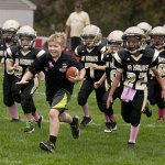 Robby 'Coach Robby' Shaffer, 9, from Prospect runs onto the field in front of the rest of the Woodland Jr. Hawks football team Saturday morning before the start of their game at Canfield Park. Robby was diagnosed with autism and being a part of the team has allowed him to participate in a team sport. –RA ARCHIVE
