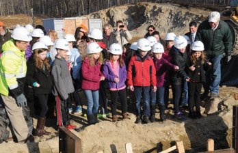 Students from Algonquin and Community schools in Prospect toss pennies into the foundation of the new Prospect Elementary School before the concrete was poured March 19. According to superstition, throwing coins into a building's foundation will bring the building, and those who inhabit it, good luck. Prospect Mayor Robert Chatfield, who invited the students to take part in the activity, said he wanted to make sure the students felt connected to the building even though some will not attend the school. –LUKE MARSHALL