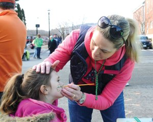 Christine Viele paints a shamrock on Logan Vitti, 5, from Bethel during the Ion Bank St. Patrick's Day Road Race and Festival Saturday in downtown Naugatuck. –LUKE MARSHALL
