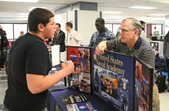 Naugatuck High School sophomore Silas Lemaire talks with Michael Molkenbuhr of the Naval Academy about the attending the academy and a career in the Navy April 2 during a college fair hosted at the school. The fair featured representatives from dozens of colleges and university, technical schools and other institutions to talk with students about their options after high school. –LUKE MARSHALL