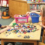 Kelly Arnold, 11, of Beacon Falls hands her brother Kenny Arnold, 8, a Lego during the Beacon Falls Public Library's Decorate the Library day June 23. Children made Lego robots and paper whirligigs that will be displayed around the library for the summer. –LUKE MARSHALL