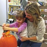 Alanna Ferrare, 5, of Beacon Falls pulls the top off of a pumpkin with the help of her mother Melinda Ferrare during the Beacon Falls Library's pumpkin carving event Oct. 29. –LUKE MARSHALL