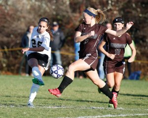 Woodland's Maribella Sousa, left, kicks the ball past Stonington's Anna Foster during the Class M quarterfinal in Beacon Falls Nov. 13. The Hawks won, 4-1, to advance to their first semifinal Tuesday where they fell, 3-2 (3-1 penalty kicks), to Enfield. –REPUBLICAN-AMERICAN