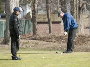 Scott Hassel takes a swing while Mayur Patel looks on during an unseasonably warm afternoon at Hop Brook Golf Course in Naugatuck Monday. –REPUBLICAN-AMERICAN