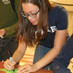 Naugatuck High School senior Alexus Coney fills out a star announcing she is attending Yale University during National Signing Day April 29 at the school. The event was part of First Lady Michelle Obama's Reach Higher Initiative. Seniors filled out stars with the name of the college or branch of the military they are going to after high school. The stars were displayed along the front hallway of the school. –LUKE MARSHALL