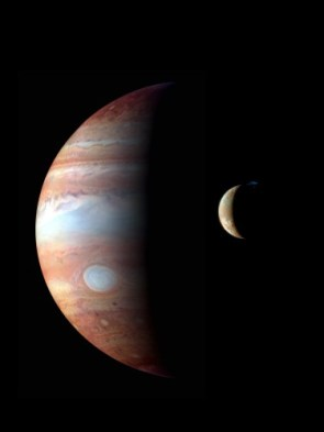 Jupiter and its moon Io. The red dot is a volcano on the moon's surface and the blue cloud is the volcano's emissions