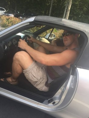 big guy in a tiny car
