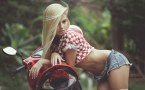 wind swept blonde leaning on a beautiful motorcycle