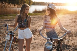 two girls in high shorts by their bikes