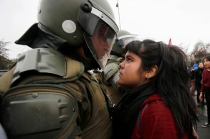 demonstrator stares down a riot policeman