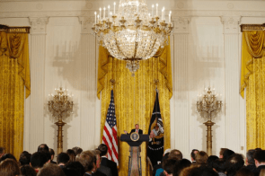 tiny trump talking in front of his pee curtains