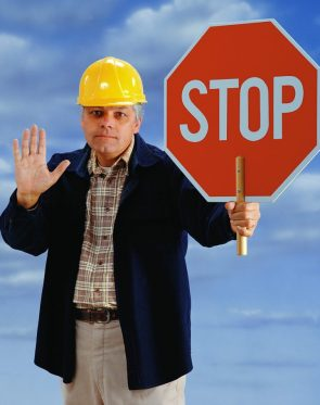 A Man In A Yellow Safety Hat Holding Up His Hand and Holding A Sign That Read STOP