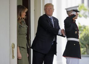 Donald Trump attempting to push a US Marine while is wife smirks