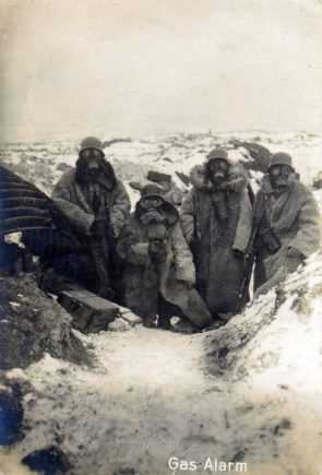 Four German soldiers wearing fur coats and gas masks in a trench, 1917