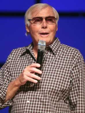 Adam West gently caresses a microphone