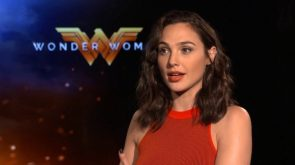 Gal Gadot sitting by Wonder Woman logo