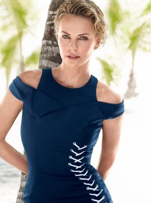 Charlize Theron leaning on a tree