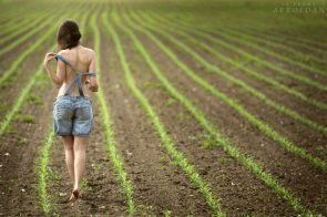 Topless woman in a field by Dani Fehr