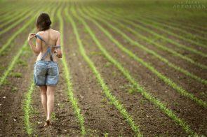 Topless woman in a field by Dani Fehr
