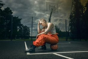 Lady Prisoner Sitting On A Basketball Under Dark Clouds While Holding Her Head