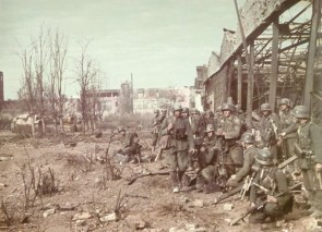 soldiers next to a destroyed building