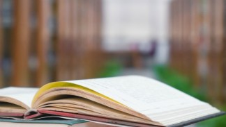 Books on the table with library background .