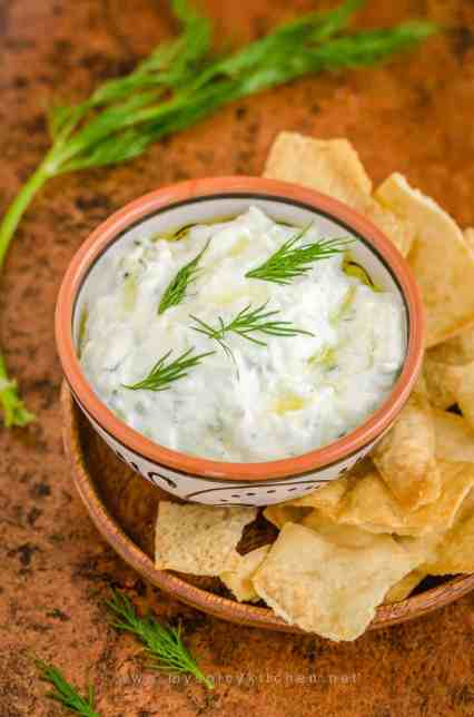 A bowl of tzatziki sauce with pita chips