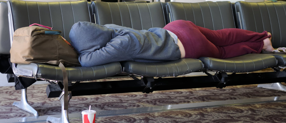 Person sleeping on the chairs in the terminal at the airport