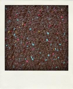 Red and green flecks on black tweed yarn