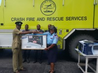 President Clarke (left) presents tv to officers in Basseterre