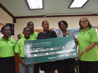 Janelle Lewis (left), Acting Permanent Secretary (PS) in the Ministry of Community Development, Gender Affairs and Social Services, Celia Christopher (2nd right), Director of Gender Affairs, Minister Phipps (right), Dion Browne (back), as well as a student, accept cheque from Silver Sponsor, The St. Kitts and Nevis-Anguilla National Bank.