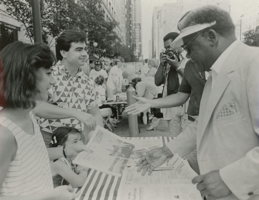 Jan and Brian Hieggelke (with their daughter Erica) show their new publication to Mayor Harold Washington at the South Loop Street Fair, 1986/Photo: Robb Perea