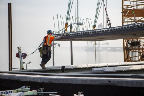 December 11, 2015 - A crew member helps guide the installation of a new road deck panel.