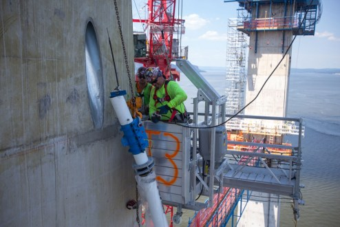 July 21, 2016 - Crews guide the project's first stay cable into an anchor point within a main span tower.