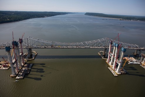 June 24, 2016 - Crews install the first sections of the main span roadway between the rising towers.