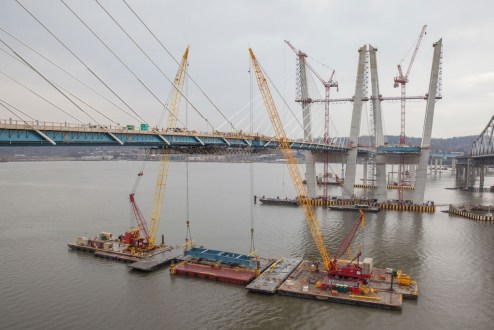 March 25, 2017 - The final section of structural steel for the westbound bridge is raised by a pair of barge-based cranes.